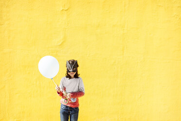 Portrait of little girl with balloon wearing animal mask in front of yellow wall - VABF000215
