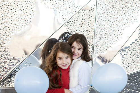 Two little girls with balloons cuddling in front of metal wall - VABF000217