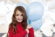 Portrait of smiling little girl with light blue balloons - VABF000220