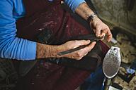 Shoemaker repairing a shoe in his  workshop, close-up - KIJF000188
