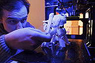 Man examining a figure of a robot printed by a 3D printer - ABZF000219