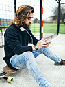 Bearded young skateboarder with smartphone and headphones - MGOF001457