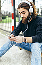 Portrait of bearded young man with smartphone and headphones - MGOF001460