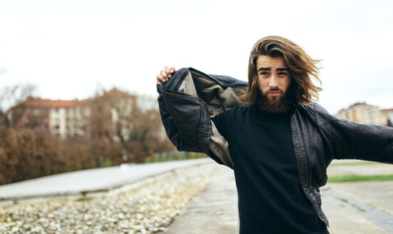 Portrait of bearded young man putting on his leather jacket - MGOF001463