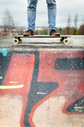 Legs of young man standing on his skateboarder - MGOF001475