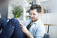 Young man at home with earbuds reading magazine - SEGF000444