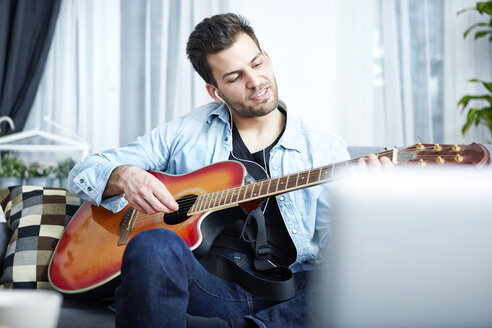 Young man at home sitting on couch playing guitar - SEGF000447