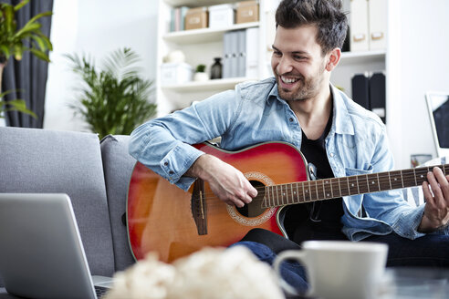 Young man at home sitting on couch playing guitar and looking at laptop - SEGF000453