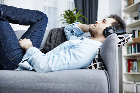 Young man at home lying on couch wearing headphones - SEGF000456