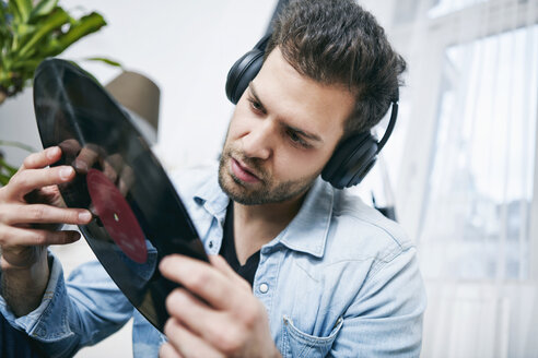 Young man wearing headphones looking at record - SEGF000462