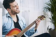 Happy young man playing guitar - SEGF000471