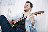 Happy young man playing guitar - SEGF000474