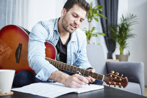 Young man with guitar composing a song - SEGF000477