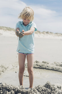 France, Brittany, Finistere, Pointe de la Torche, boy playing with sand on the beach - MJF001787
