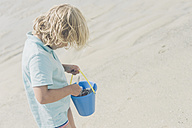 France, Brittany, Finistere, Pointe de la Torche, boy on the beach looking in bucket - MJF001793