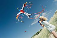 France, Brittany, Cap Frehel, Cote d'Emeraude, boy flying kite in beach dune - MJF001817