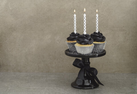 Three cup cakes with black buttercream topping and lighted candles on a cake stand - ECF001859