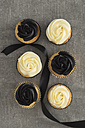 Six cup cakes with black and cream coloured buttercream topping and black ribbon - ECF001862