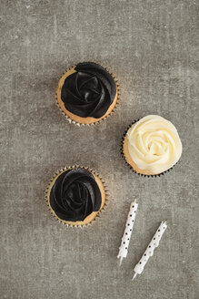 Cup cakes with black and cream coloured buttercream topping and two candles - ECF001865