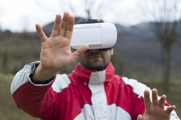 Man playing with Virtual Reality Glasses in nature - SKCF000074