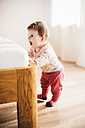 Happy baby girl standing at the edge of a bed - BRF001261
