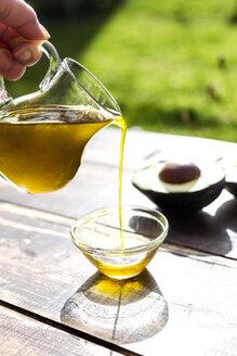 Pouring avocado oil into glass bowl - SARF002592