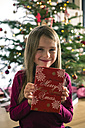 Portrait of happy girl holding Christmas present - SARF002595