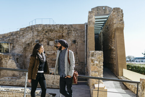 Spain, Tarragona, Young couple talking as they walk around the city - JRFF000451