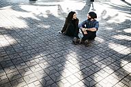 Spain, Tarragona, Young couple talking, sitting in shadow - JRFF000466