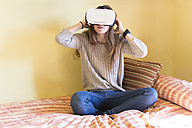 Young woman with Virtual Reality Glasses sitting on her bed at home - SKCF000075