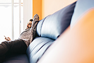 Bearded young man working at home relaxed sitting on the couch, using laptop and mobile - JRFF000475