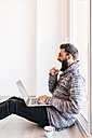 Bearded young man working at home relaxed, sitting on the floor, using laptop - JRFF000478