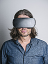 Portrait of man wearing Virtual Reality Glasses in front of grey background - KRPF001734