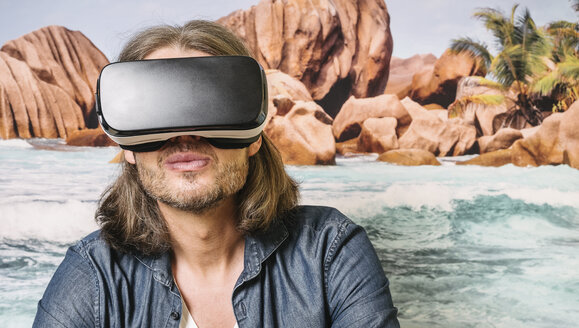 Portrait of man wearing Virtual Reality Glasses in front of photographic wallpaper - KRPF001737