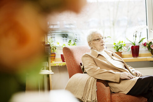 Portrait of senior woman with Alzheimer's disease sitting in her room at retirement home - JATF000845