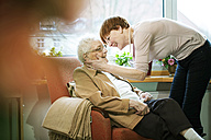 Adult daughter greeting her mother with Alzheimer's disease in her room at retirement home - JATF000848