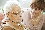 Portrait of senior woman with Alzheimer's disease with her adult daughter watching in the background - JATF000851