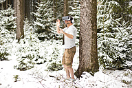 Man wearing Virtual Reality Glasses in winter landscape - MAEF011364