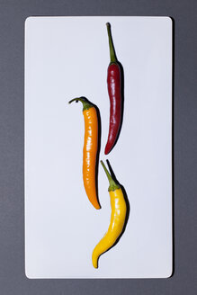 Three different chili pods on white board - MN000155
