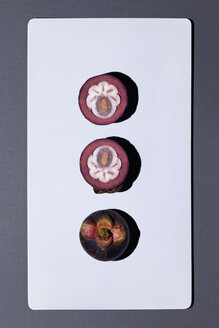 Whole and sliced mangosteen on white board - MN000158