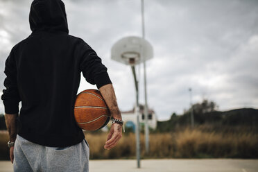 Man playing with basketball on an outdoor court - JRFF000480