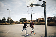 Two young men playing basketball on an outdoor court - JRFF000483