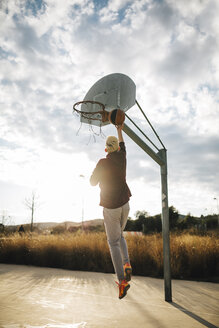 Young man playing basketball on an outdoor court - JRFF000486