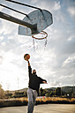 Young man playing basketball on an outdoor court - JRFF000489