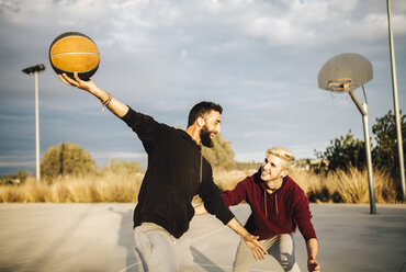 Two young men playing basketball on an outdoor court - JRFF000492