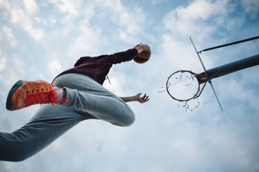 Young man playing basketball on an outdoor court - JRFF000495