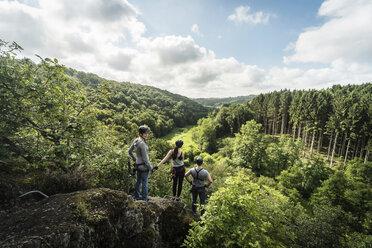 Germany, Westerwald, Hoelderstein, three friends on via ferrata looking at view - PAF001554