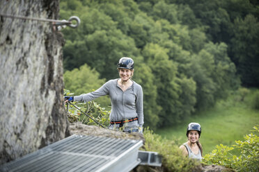 Germany, Westerwald, Hoelderstein, two smiling women climbing on via ferrata - PAF001557