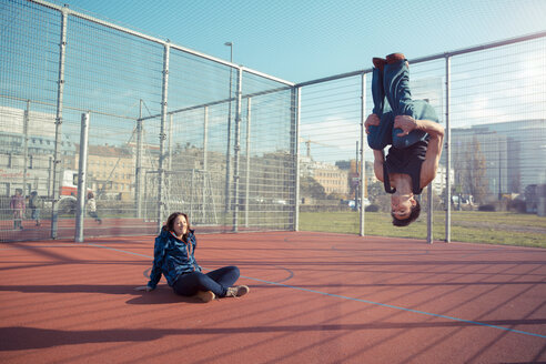 Young man on sports field doing a somersault - SUF000072