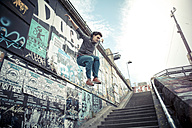 Young man jumping off wall - SU000075